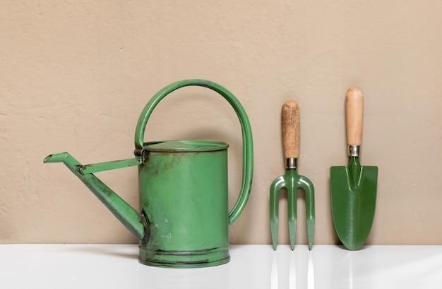 Set von kleinen grünen gartengeräten einschließlich einer altmodischen gießkanne, kelle und gabel