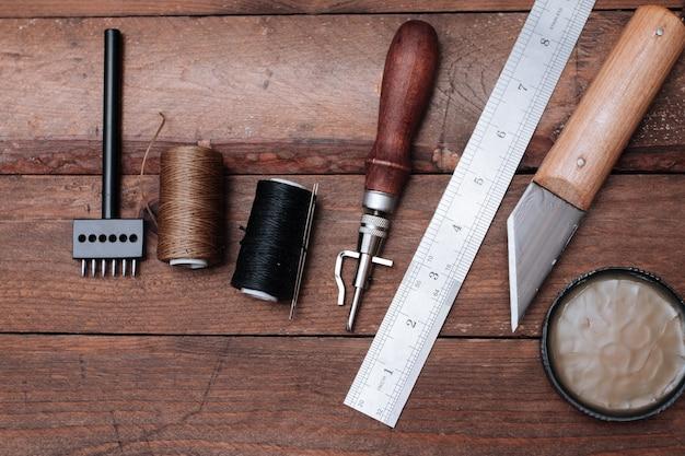 Set von lederhandwerkswerkzeugen. schuhmacherwerkzeuge auf holztisch.