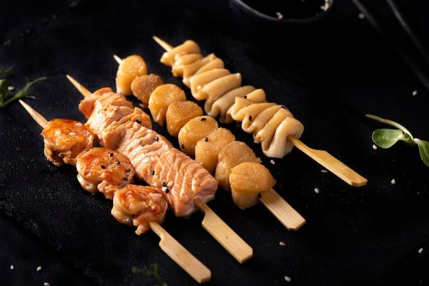 Set von meeresfrüchte-kebabs mit sojasauce und sesam auf schwarzem brett