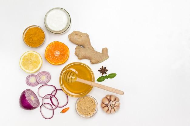 Set von produkten aus zitrusfrüchten, ingwer, honig, knoblauch, zwiebeljoghurt zum natürlichen schutz vor dem virus. medizinische ernährung zu hause. flach liegen. speicherplatz kopieren