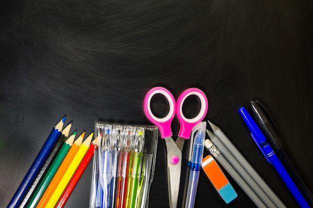 Set von schulpapieren. kugelschreiber, bleistifte, scheren und radiergummi auf tafel. zurück zum schulkonzept