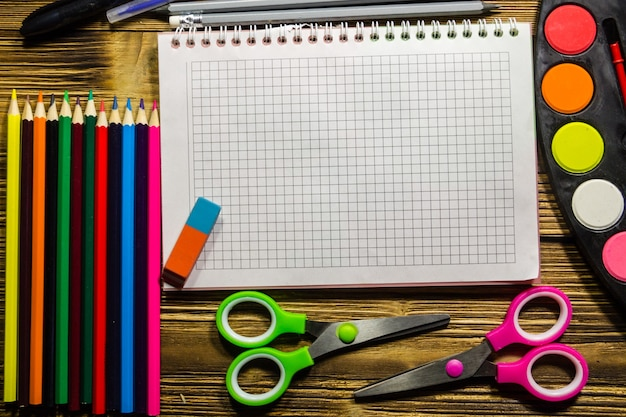 Set von schulpapieren. leeres notizbuch, buntstifte, stifte, aquarellfarben, scheren, pinsel und radiergummi auf holzschreibtisch. zurück zum schulkonzept
