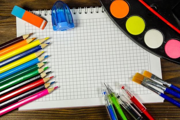Set von schulpapieren. leeres notizbuch, buntstifte, stifte, aquarellfarben und andere gegenstände auf dem schreibtisch aus holz. zurück zum schulkonzept