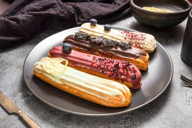 Set von verschiedenen eclair-kuchen auf dunklen hintergrund