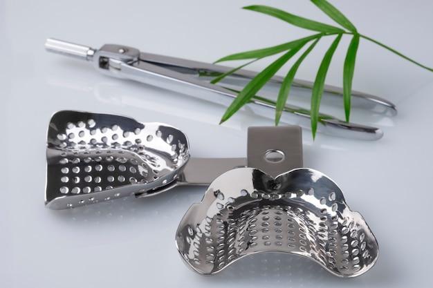 Set von zahnärztlichen kompassen und bissregistrierbechern für zahnärztliche abdrücke beim zahnarzt