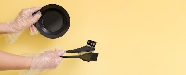 Set zum färben von haaren zu hause oder im salon in den händen einer frau mit handschuhen. bürsten und schüssel für haarfärbemittel auf gelbem hintergrund. bannerformat mit textfreiraum