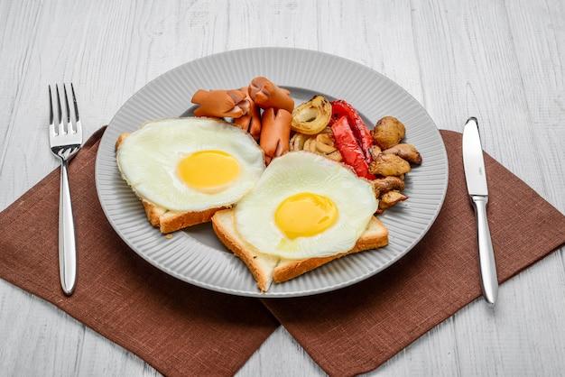 Set zum frühstück spiegeleier, gegrilltes gemüse, würstchen. brot auf einem holztisch.
