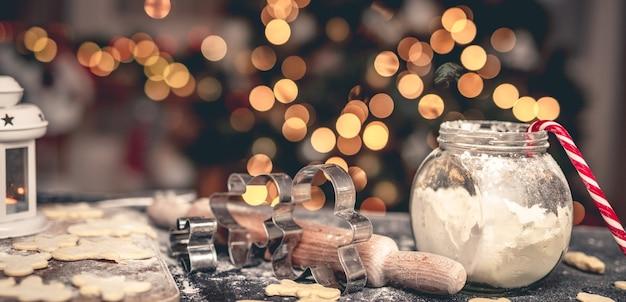 Set zum lebkuchenbacken auf dem tisch vor dem weihnachtsbaum