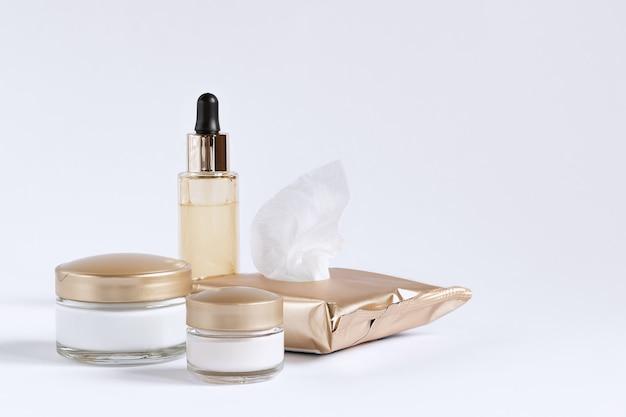 Set zur pflege der haut um die augen und der haut bestehend aus reinigungstüchern, gläsern mit sahne und einer flasche mit einer serumpipette