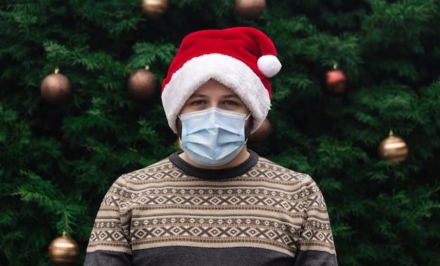 Setzen sie eine medizinische maske richtig auf. schließen sie herauf porträt des mannes, der einen weihnachtsmannhut, weihnachtspullover und medizinische maske mit emotion trägt. vor dem hintergrund eines weihnachtsbaumes. coronavirus pandemie