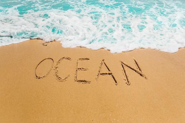Setzen sie hintergrund mit dem ozean auf den strand, der in sand geschrieben wird