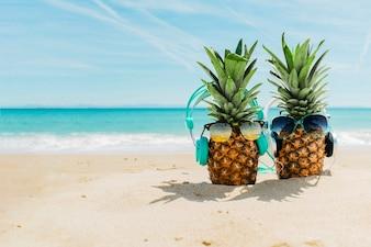 Setzen Sie Hintergrund mit den kühlen Ananas auf den Strand, die Kopfhörer tragen