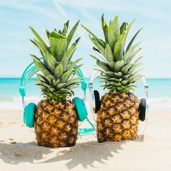 Setzen sie hintergrund mit zwei ananas auf den strand, die kopfhörer tragen