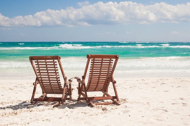 Setzen sie holzstühle für ferien auf den strand und entspannen sie sich auf tropischem strand in tulum, mexiko
