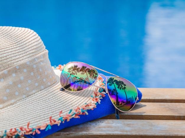 Setzen sie hut mit sonnenbrille an der seite des swimmingpools für sommerkonzept auf den strand