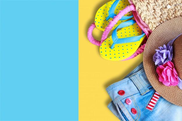 Setzen sie zubehör auf gelbem und blauem farbhintergrund auf den strand, legen sie flach foto