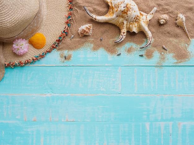 Setzen sie zubehör auf hellem blauem hölzernem pastellhintergrund für sommerferien und ferien auf den strand