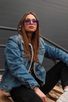 Sexy amerikanische junge hipster-frau in stilvoller lila brille in einer blauen jeansjacke der jugend entspannt sich draußen in der nähe des grauen gebäudes. schönes mädchenmodell in freizeitkleidung auf der straße. jugendstil im frühling.