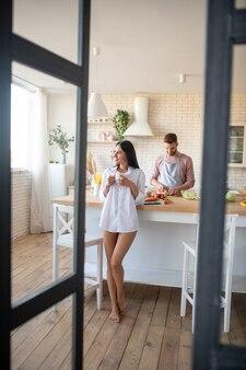 Sexy ansprechende frau, die kaffee trinkt, während ehemann in der geräumigen küche kocht