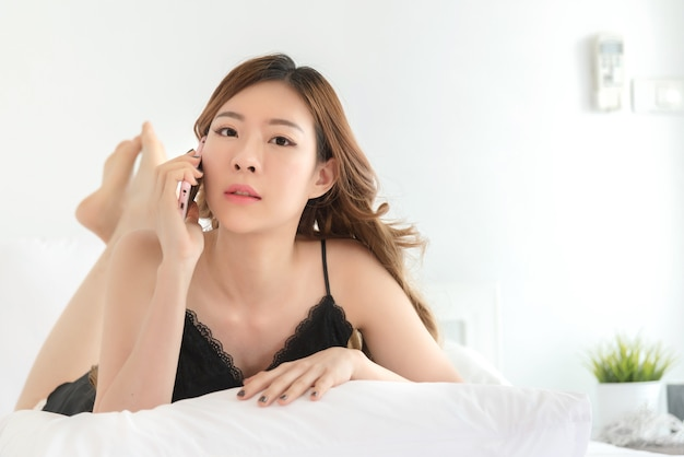 Sexy asiatische dünne frau, die im bett aufwirft