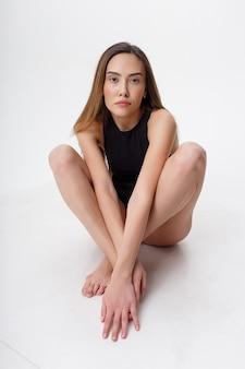 Sexy asiatische dünne frau mit langen haaren in schwarzen dessous, die auf boden sitzen