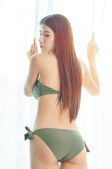 Sexy asiatische frau im bikinigrün auf dem schlafzimmer im urlaub