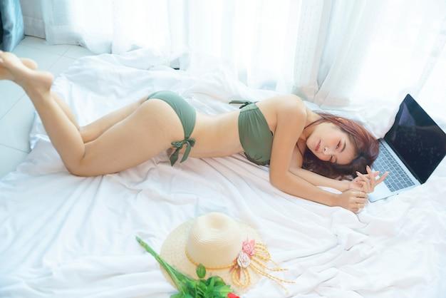 Sexy asiatische frau im bikinigrün, die auf dem bett liegt