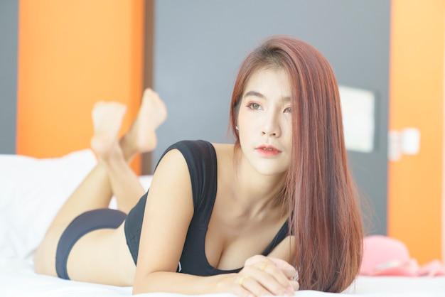 Sexy asiatische frau im schwarzen bikini, die auf dem bett liegt
