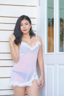 Sexy asiatische frau im weißen kleid auf dem schlafzimmer