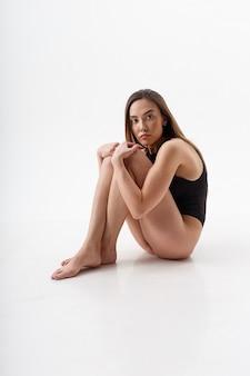 Sexy asiatische frau mit dem langen haar, das in den schwarzen dessous auf weißem studiohintergrund mit nackten füßen aufwirft. attraktive frau, die mit gebeugten knien auf dem boden sitzt. modellversuche der skinny lady im body