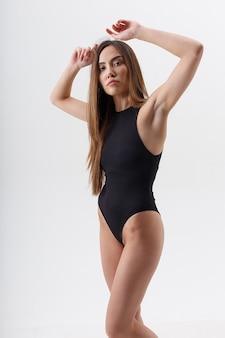 Sexy asiatische frau mit langen haaren, die in schwarzen dessous auf weißem studiohintergrund mit erhobenen armen aufwerfen. attraktives weibliches stehen. modellversuche der skinny lady im body