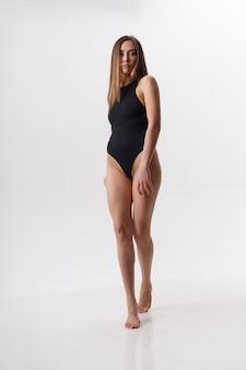 Sexy asiatische frau mit langen haaren posiert in schwarzen dessous mit nackten füßen