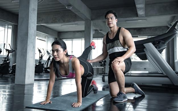 Sexy asiatische frau workout unterschenkel auf einer yogamatte mit trainer mann im fitnessstudio.