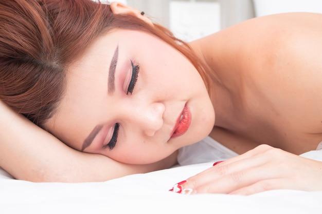 Sexy asiatisches mädchen, das auf bett schläft