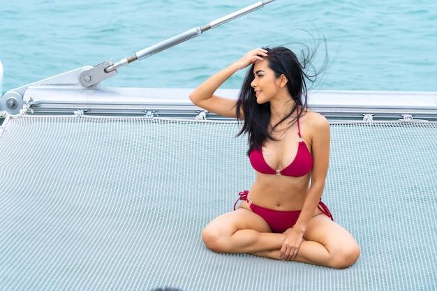 Sexy asiatisches mädchen des porträts im bikini setzen sich hin, entspannend auf kreuzfahrtyacht mit hintergrund von meer des blauen wassers konzeptluxusreise mit natur von meer.