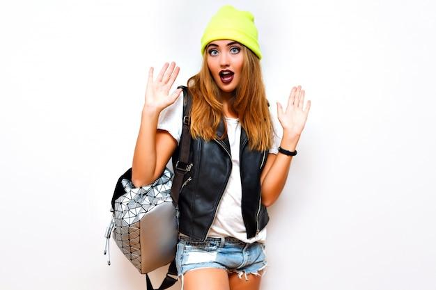 Sexy atemberaubende modefrau posiert in der nähe von weißer wand, streetstyle-hipster-look, biker-lederweste, mini-shorts, neonhut und rucksack, gebräunter sexy git-körper, yo, beute, sommer, blitz, lustig, verrückt