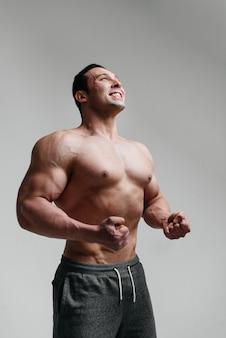 Sexy athlet, der auf einem weißen hintergrund oben ohne aufwirft. fitness.