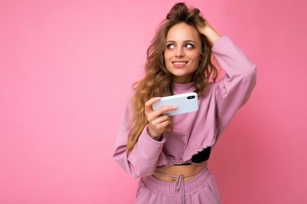 Sexy attraktive blonde junge frau mit rosa kapuzenpulli isoliert über rosa hintergrund mit kopienraum, der das handy hält und zur seite schaut.