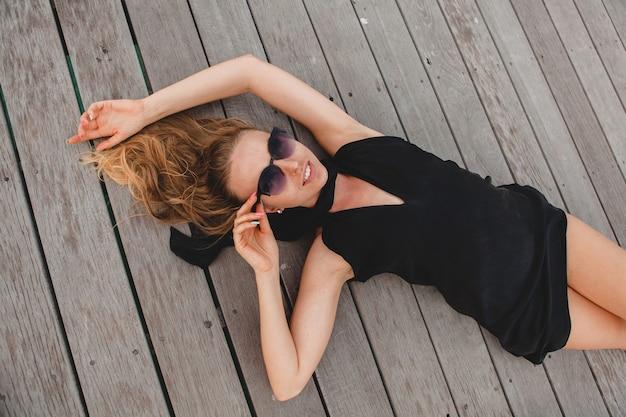 Sexy attraktive luxusfrau gekleidet im schwarzen kleid, das auf dem boden liegend trägt sonnenbrille, sommerferien, ansicht von oben