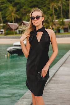 Sexy attraktive luxusfrau gekleidet im schwarzen kleid, das auf pier im luxusresorthotel aufwirft, sonnenbrille tragend, sommerferien, tropischer strand