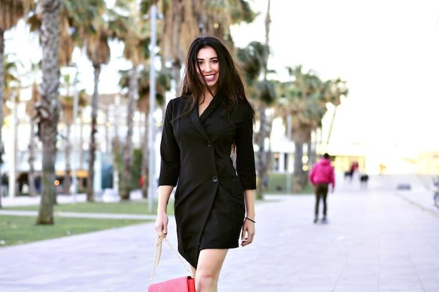 Sexy attraktive selbstbewusste frau, die straße mit palmen geht, modernistisches minimalistisches schwarzes kleid der geschäftsfrau, das bei spanien reist.
