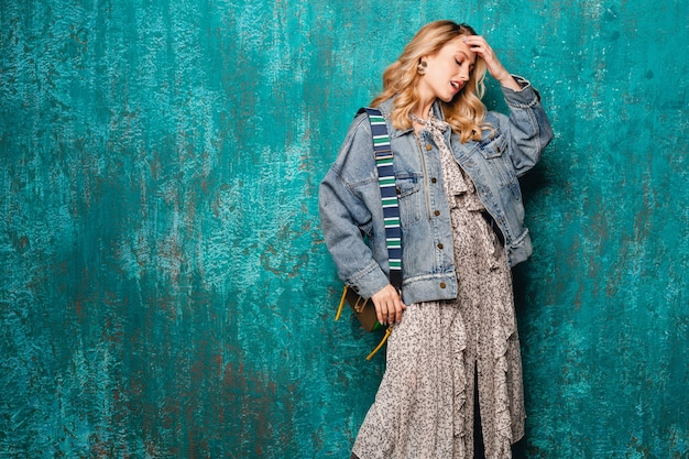 Sexy attraktive stilvolle blonde frau in jeans und übergroße jacke, die gegen vintage grüne wand in der straße geht