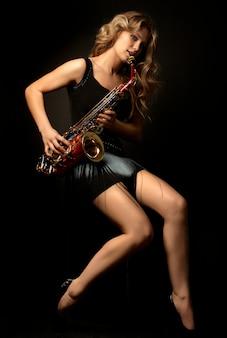 Sexy attraktives blondinemodell mit saxophon