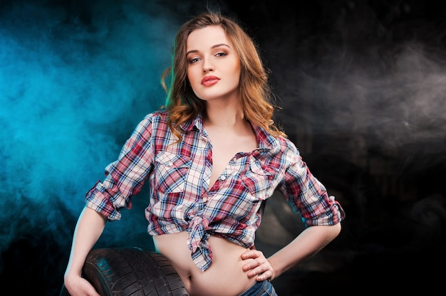 Sexy automechaniker. schöne junge frau, die sich am autoreifen lehnt und in die kamera schaut, während sie in der autowerkstatt steht