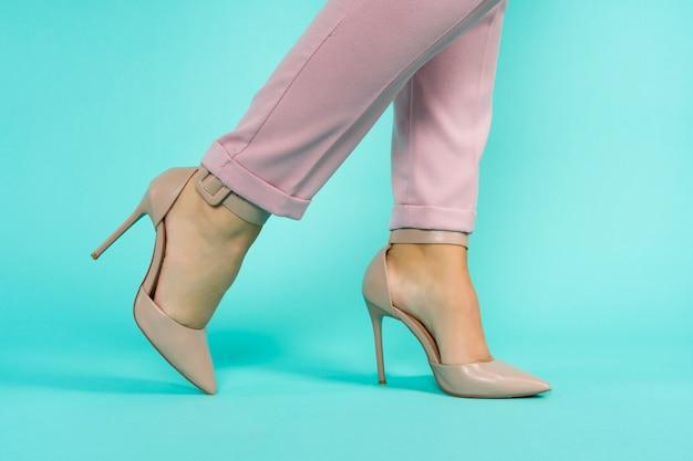 Sexy beine in braunen high heels schuhen auf blauem hintergrundbild