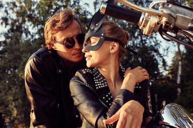 Sexy bikerpaar auf dem vintage custom-motorrad, mädchen in einer kaninchenmaske. junge schöne paar-hipster in stilvoller kleidung für motorrad auf der straße, outdoor-porträt