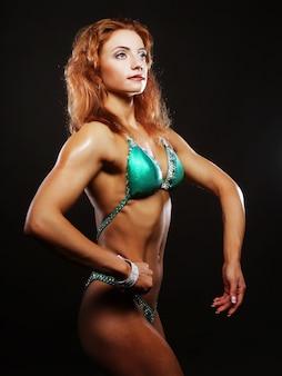 Sexy blonde bodybuilderfrau im bikin auf schwarzem hintergrund