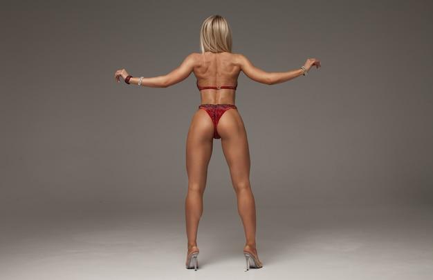 Sexy blonde bodybuilderfrau im bikini auf grauem hintergrund