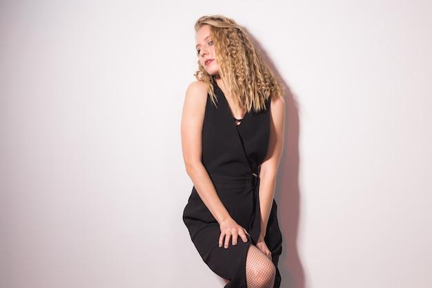 Sexy blonde elegante frau im schwarzen kleid, die auf weißem hintergrund mit kopienraum steht