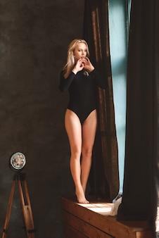 Sexy blonde frau im bodysuit zu hause in der nähe einer lampe, taschenlampe. perfekte figur, schöner körper.